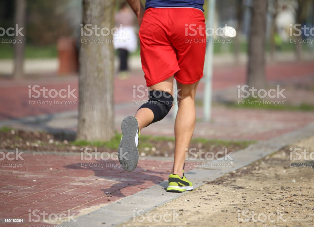 runner training with knee bandage for problems with leg joints stock photo