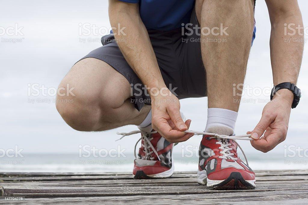Runner tying shoelace royalty-free stock photo