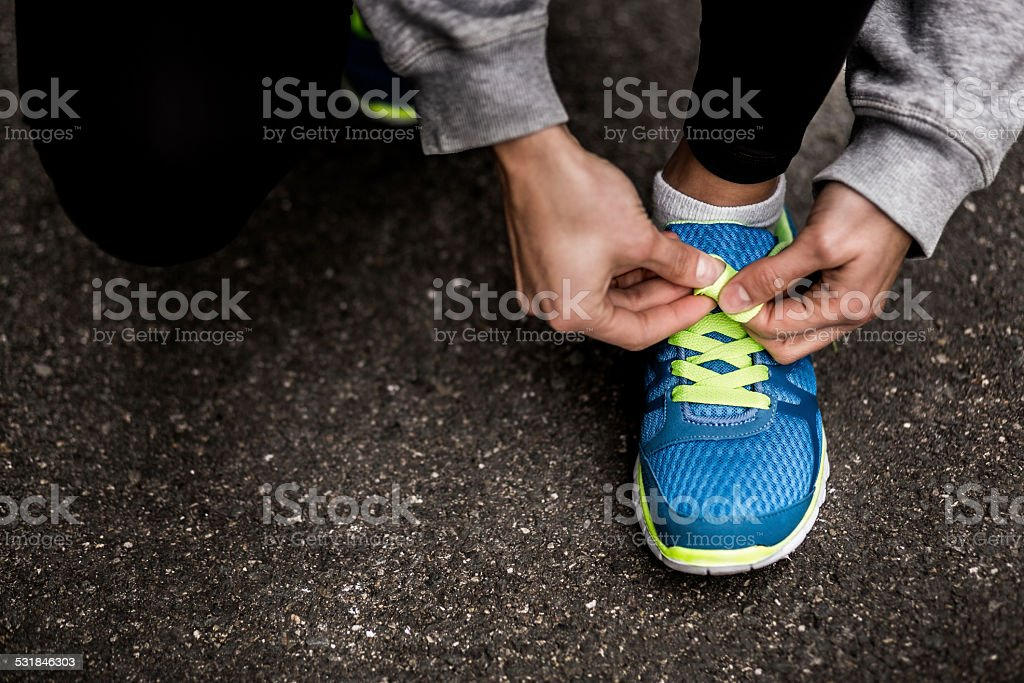 Runner Tying Shoelaces In The Road stock photo
