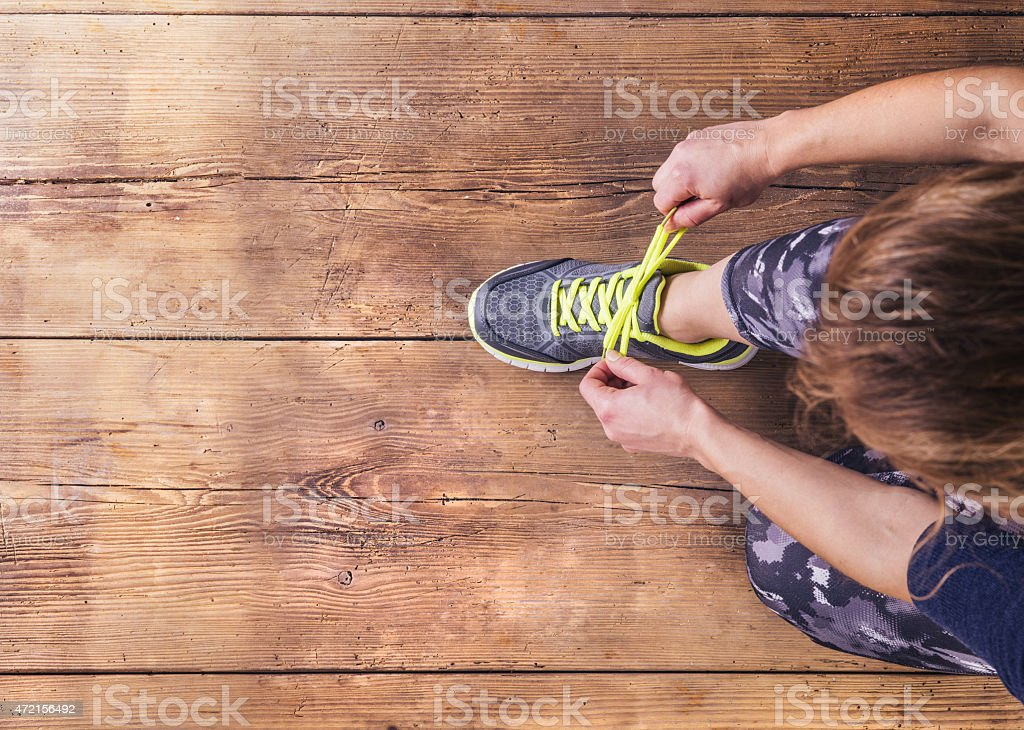 A runner tying up her laces, shot from above stock photo