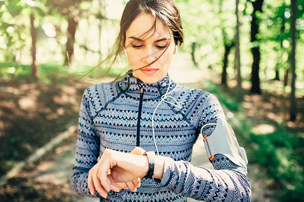 Runner using smart watch Runner using smart watch woman taking pulse stock pictures, royalty-free photos & images