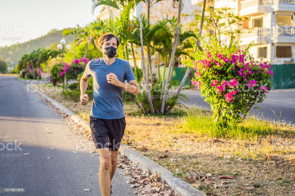 Runner wearing medical mask, Coronavirus pandemic Covid-19. Sport, Active life in quarantine surgical sterilizing face mask protection. Outdoor run on athletics track in Corona Outbreak. Keep your shape during quarantine, pandemic. - Foto stock royalty-free di Abbigliamento
