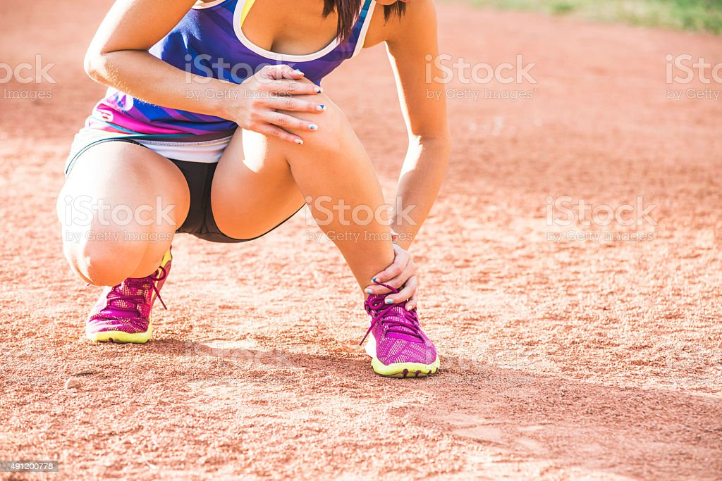 runner with ankle injury holds foot to reduce pain stock photo