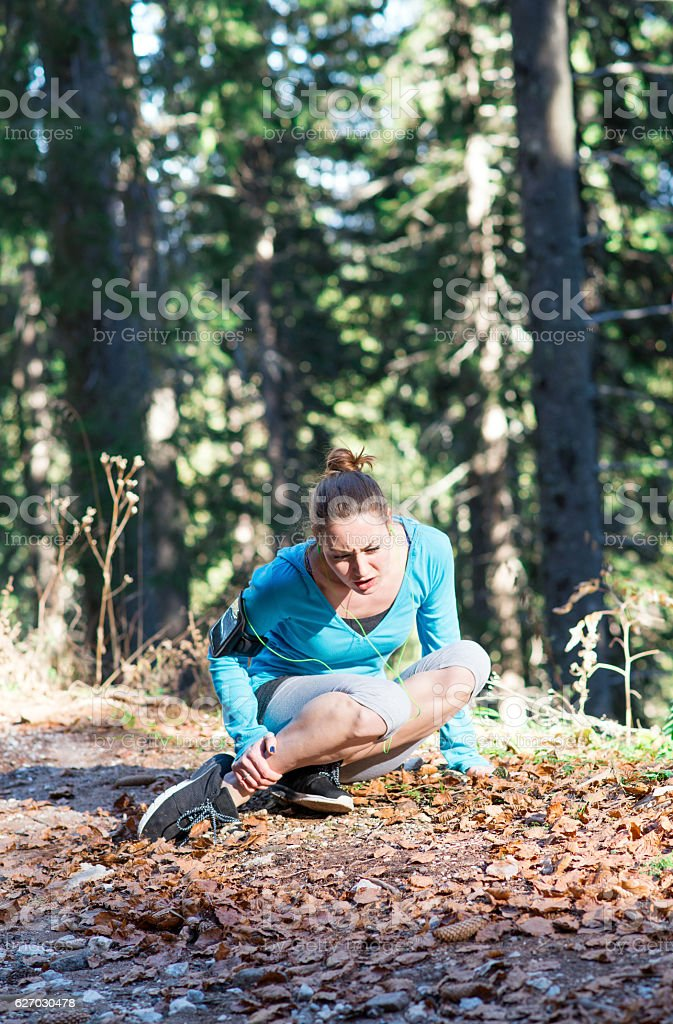 Runner with ankle injury holds foot to reduce pain. stock photo