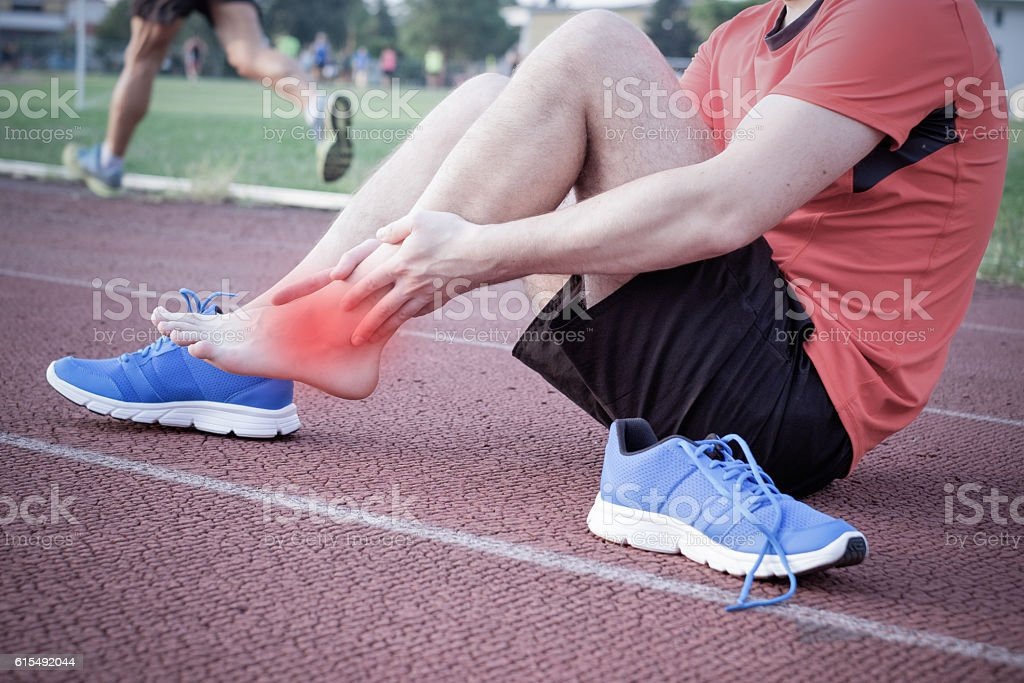 Runner with injured ankle on the track stock photo