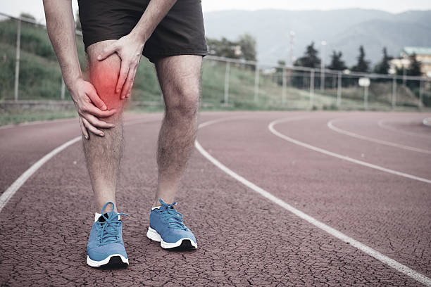 runner with injured knee on the track - human knee stock photos and pictures