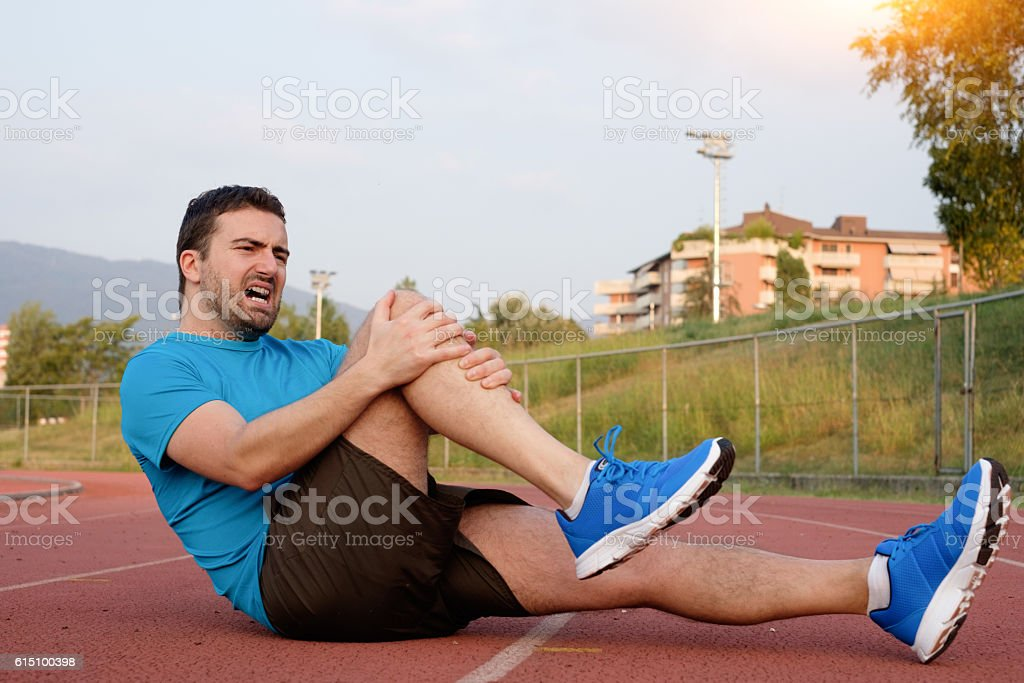 Runner with injured knee on the track stock photo