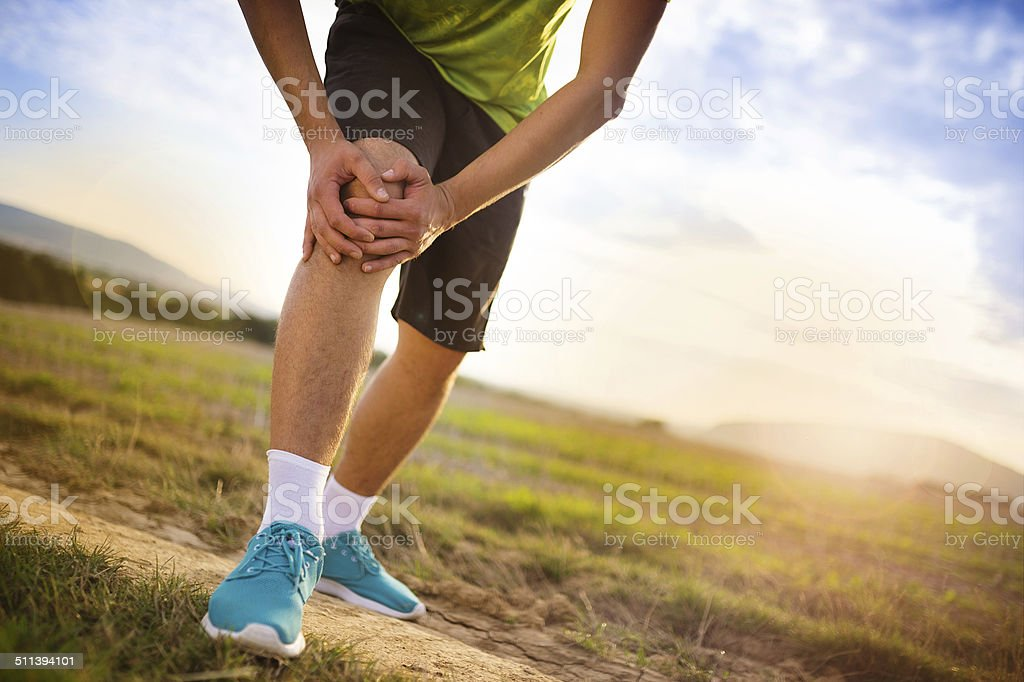 Runner with injured knee stock photo