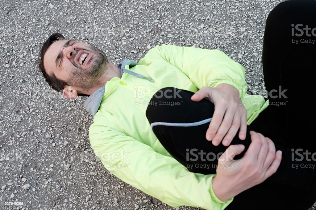 Runner with injured knee while training stock photo
