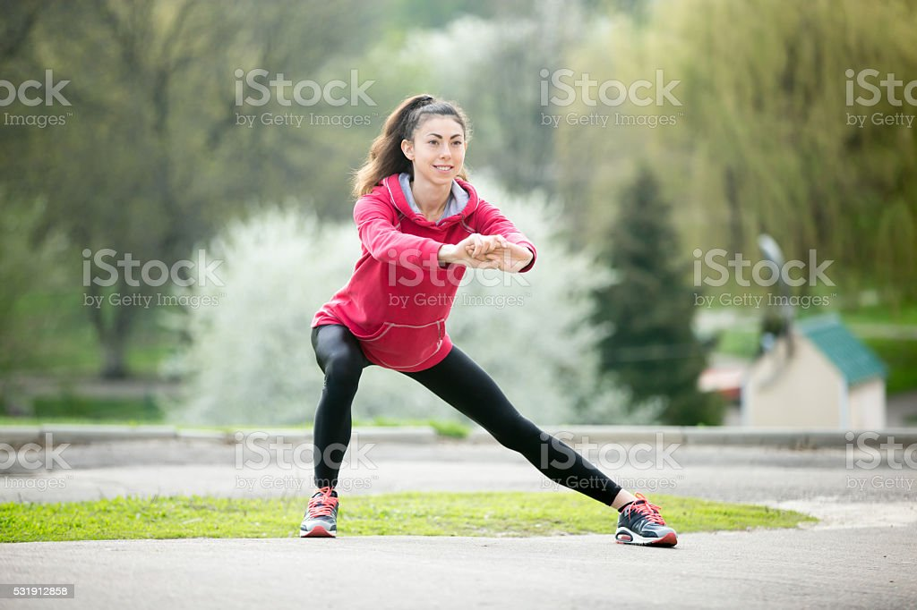 Runner woman doing side lunges before jogging stock photo