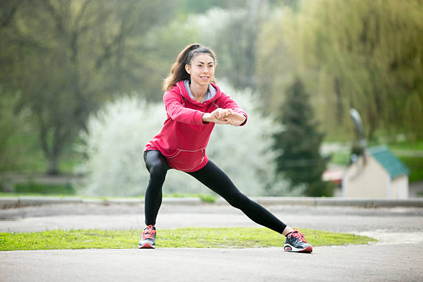 runner woman doing side lunges before jogging - lunge stock photos and pictures