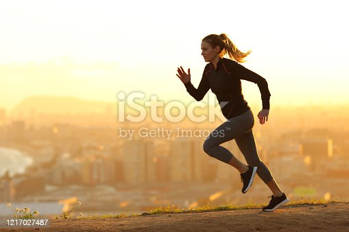 Side view full body portrait of a runner woman running in the outskirts of the city at sunset