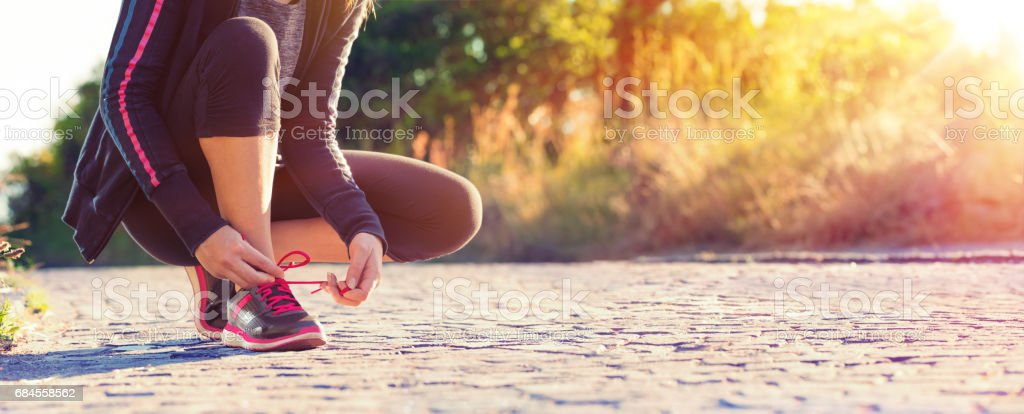 Runner Woman Tying Her Shoelaces While Jogging stock photo