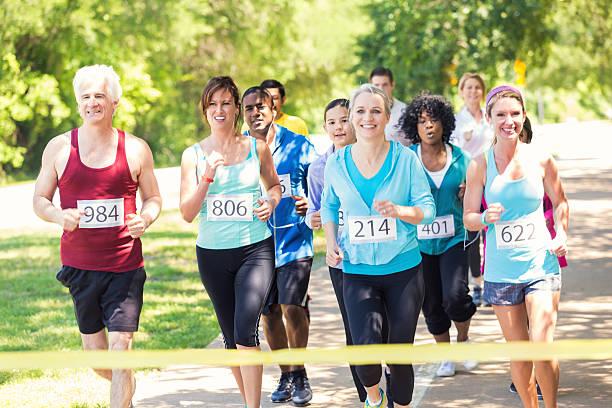 läufer nähern ziellinie während marathon oder 5 km lauf - laufveranstaltungen stock-fotos und bilder
