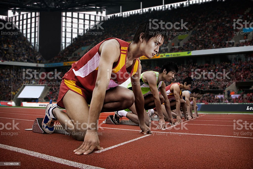 Runners at starting line in stadium royalty-free stock photo