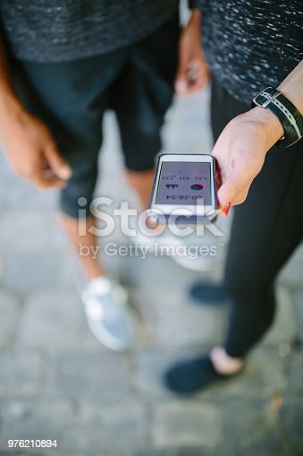 istock Runners checking their workout performance on phone app 976210894
