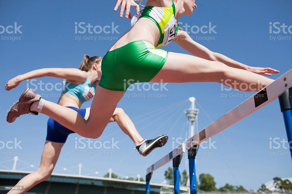 Runners jumping hurdles on track stock photo