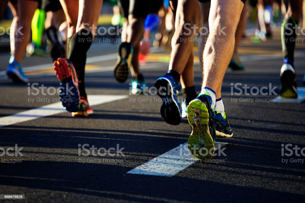 Runners legs from behind on the road stock photo