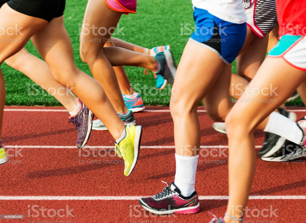 Runners legs on a red track stock photo
