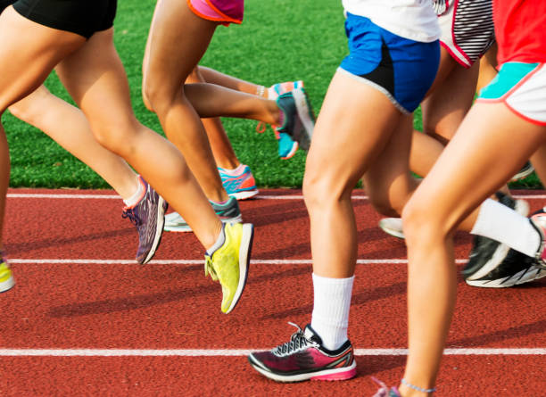 runners legs on a red track - high school sports stock pictures, royalty-free photos & images