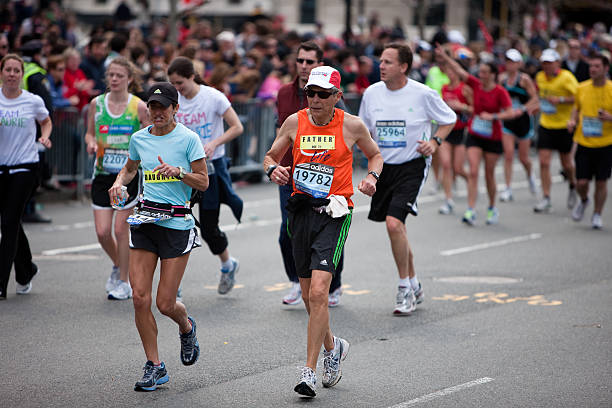 runners near the finish line of the boston marathon - boston marathon stock photos and pictures