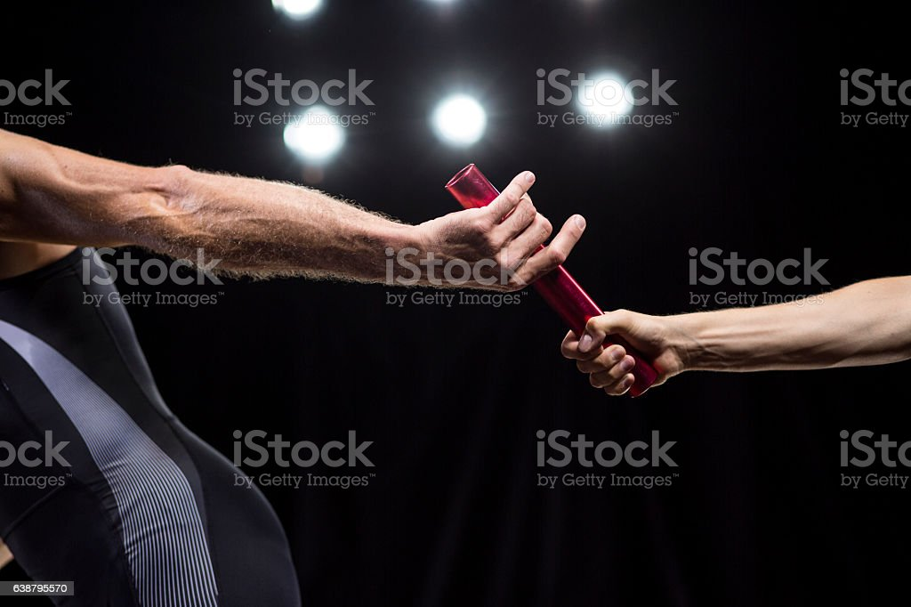 Runners passing baton stock photo
