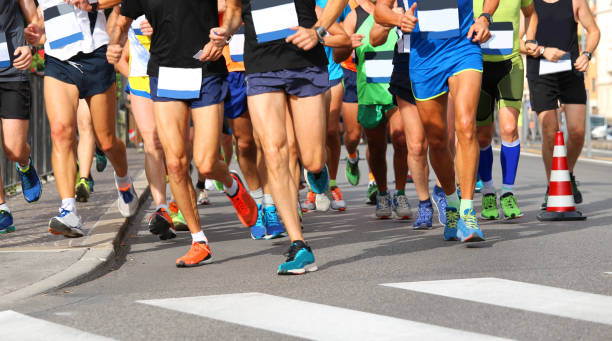 runners run at finish line during race in the city - sports event stock photos and pictures