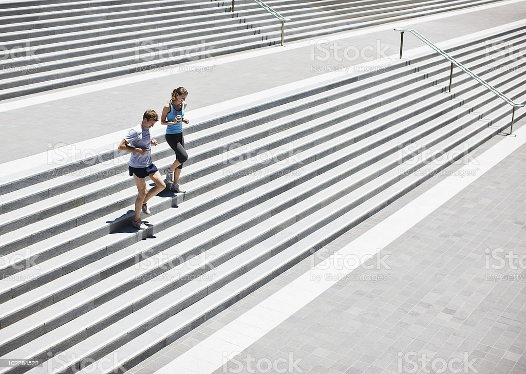 Runners running down stairs stock photo
