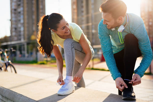 Runners tying running shoes and getting ready to run stock photo