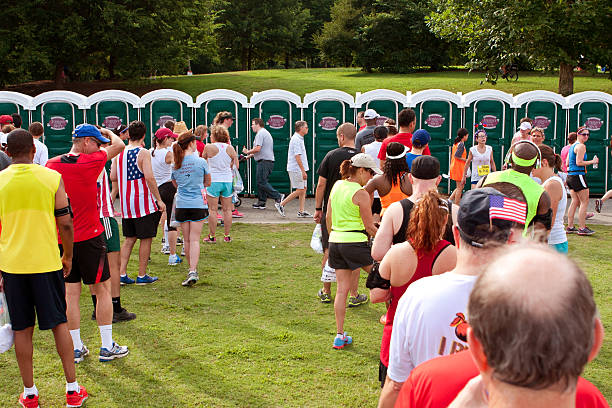 10K Runners Wait In Line To Use Portable Toilets Atlanta, GA, USA - July 4, 2014:  Exhausted runners wait in long lines to use a Johnny On The Spot portable toilet, after just completing the Peachtree Road Race 10K. portable toilet stock pictures, royalty-free photos & images