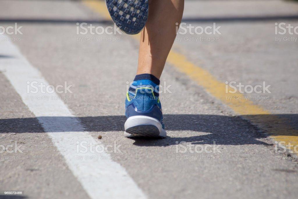 runnesr feet back race on asphalt action , background royalty-free stock photo