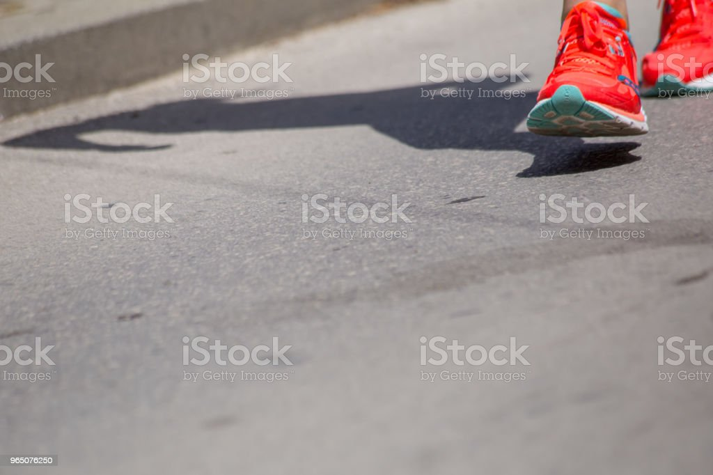 runnesr feet back race on asphalt action , background royalty-free stock photo