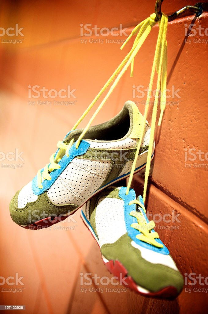 runnig shoes hanging on a wall stock photo