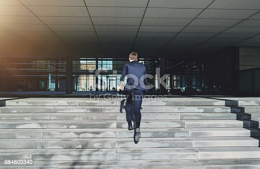 684803840istockphoto Runnig upstairs fast man wearing blue suit 684803340