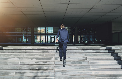 684803840 istock photo Runnig upstairs fast man wearing blue suit 684803340