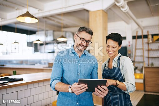 Shot of a man and woman using a digital tablet together in their coffee shop