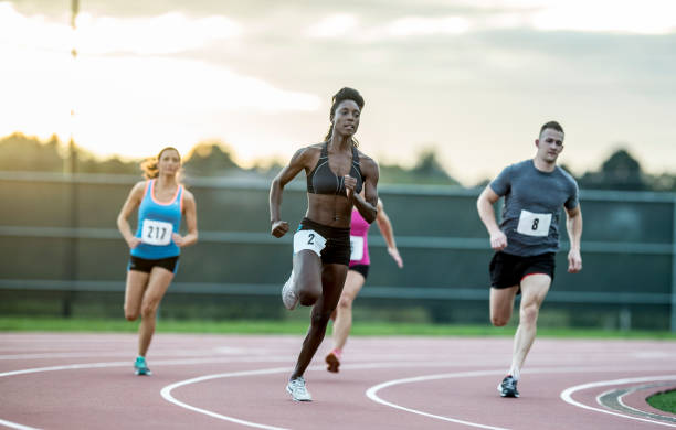 Running A Race A multi-ethnic group of sprinters are running on a racetrack. They are wearing athletic clothing and shoes, and they have racing numbers. They are running with the sunset in the background. women's track stock pictures, royalty-free photos & images