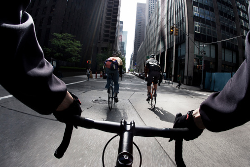 The handlebar view of three male bicycle messengers riding their single speed bikes through a yellow light at an intersection in New York City.