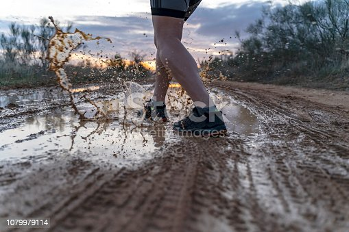986840244 istock photo Running across the puddles, at sunset in shorts, with sneakers, along a path. 1079979114
