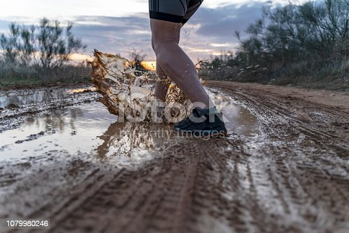 986840244 istock photo Running across the puddles, at sunset in shorts, with sneakers, along a path. 1079980246