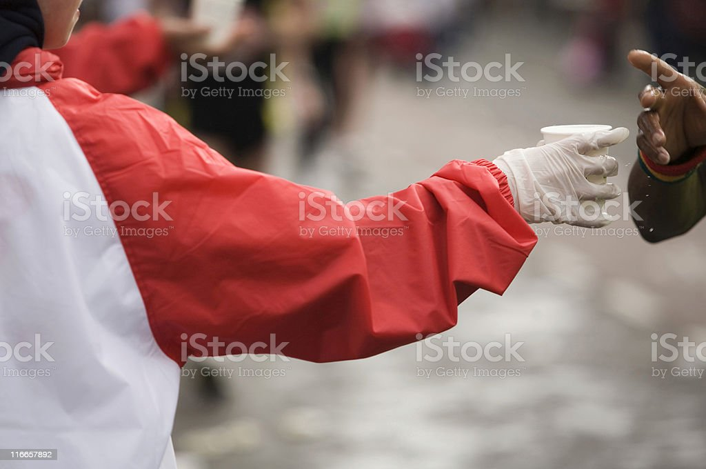 running African athlete grabbing for a drink royalty-free stock photo
