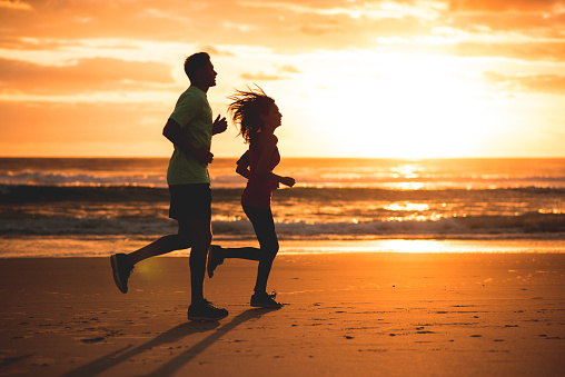 Silhouette shot of young couple running on a beach at sunset. Sea in back. Lit from behind.
