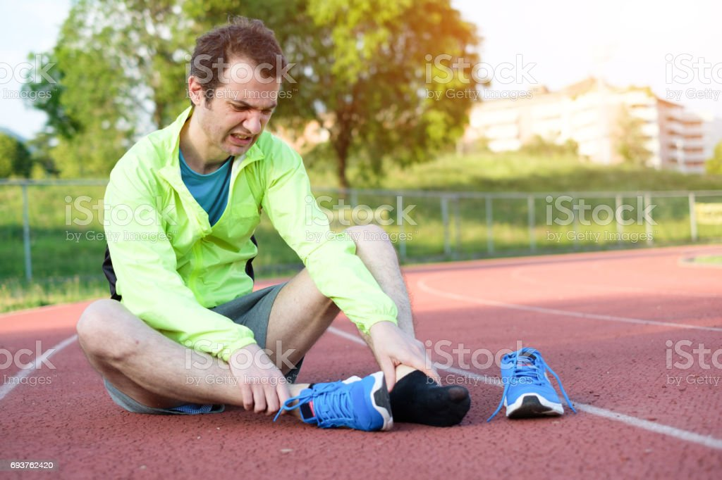 Running athlete feeling pain because of injured ankle stock photo