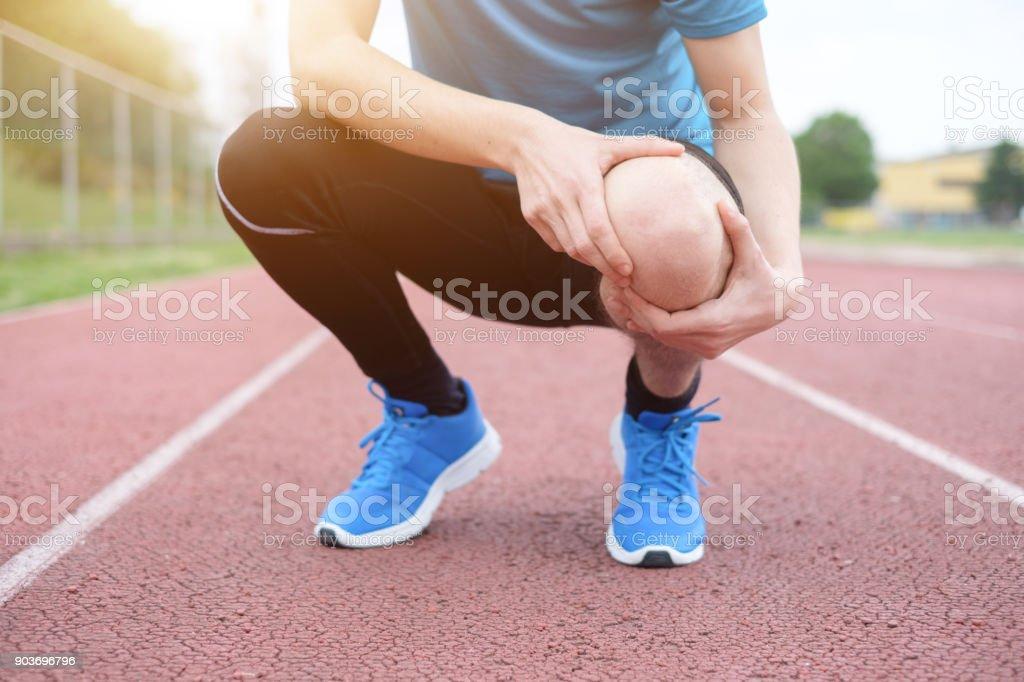 Corriendo atleta sensación de dolor debido a la rodilla lesionada - foto de stock