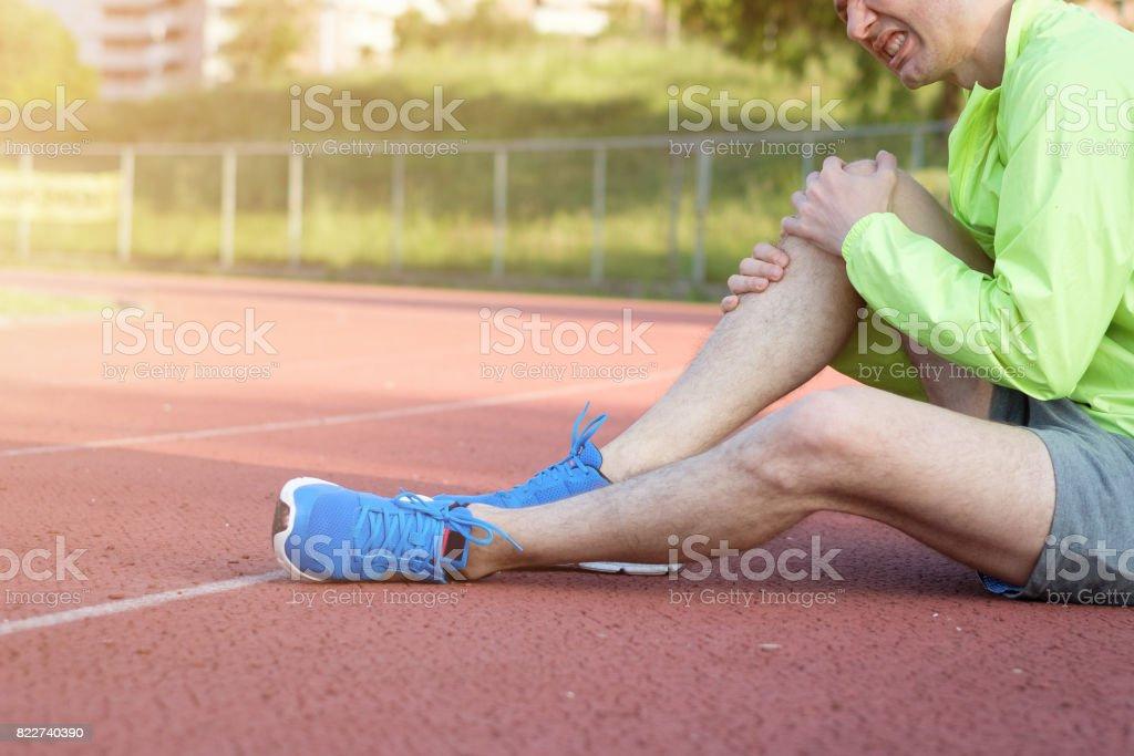 Running athlete feeling pain because of injured leg stock photo