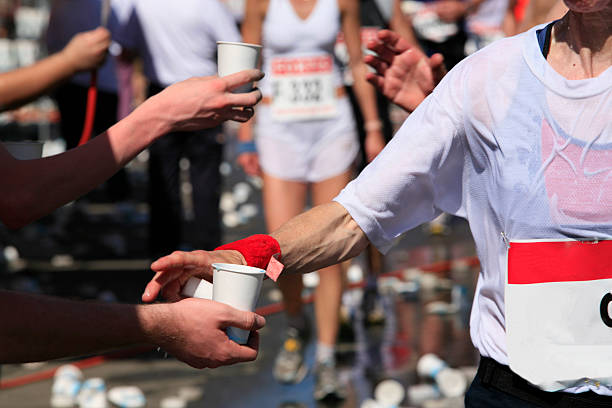 Running athletes grabbing water offering drink to athletes at a long distance run race distance stock pictures, royalty-free photos & images