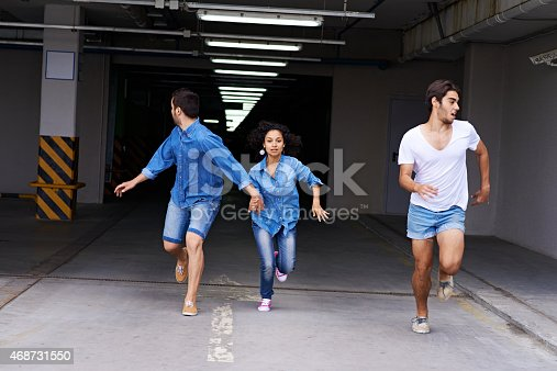Young people running from parking garage and one young man looking back