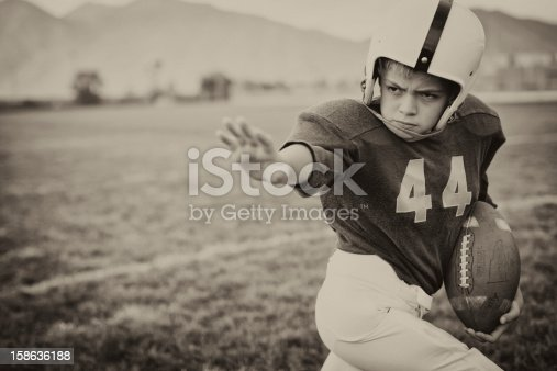 A young American Football boy applies the straight arm. It is football time. Vintage theme.