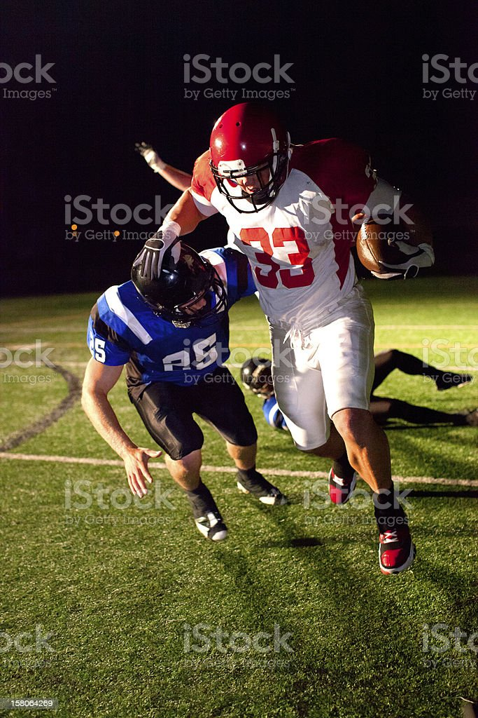 Running back stiff arms defender stock photo