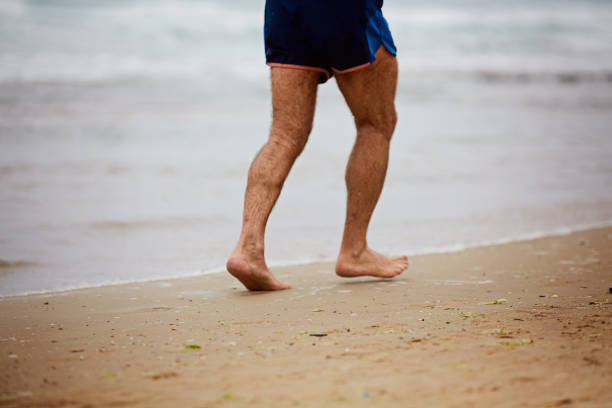 running bare legs of male runner jogging on beach. - old man feet stock photos and pictures